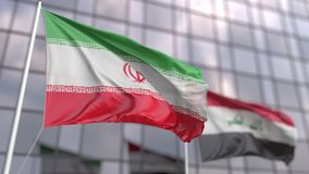 Waving flags of Iran and Iraq in front of a modern skyscraper facade