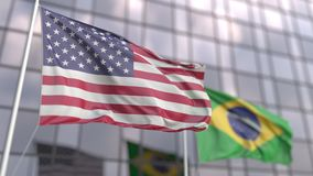 Waving flags of the United States and Brazil in front of a modern skyscraper facade