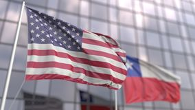 Waving flags of the United States and Chile in front of a modern skyscraper facade