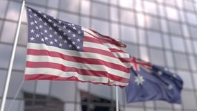 Waving flags of the USA and Australia in front of a modern skyscraper facade