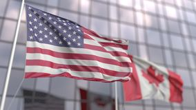 Waving flags of the USA and Canada in front of a modern skyscraper facade