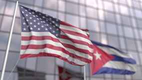 Waving flags of the USA and Cuba in front of a modern skyscraper facade