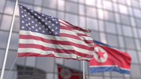 Waving flags of the USA and North Korea in front of a modern skyscraper facade