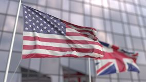 Waving flags of the USA and the UK in front of a modern skyscraper facade