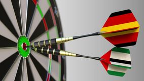 Flags of Germany and the UAE on darts hitting bullseye of the target. International cooperation or competition. Animation stock footage