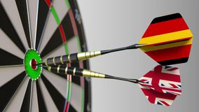 Flags of Germany and the United Kingdom on darts hitting bullseye of the target. International cooperation or. Competition animation stock video