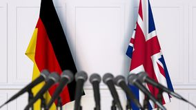 Flags of Germany and the United Kingdom at international meeting or negotiations press conference. 3D animation stock video footage
