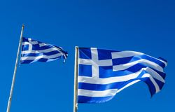 Flags of Greece Flying in Wind and Blue Sky Stock Images