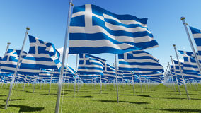 Flags of Greece in green field against blue sky. Royalty Free Stock Photos
