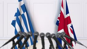Flags of Greece and The United Kingdom at international meeting or negotiations press conference. 3D animation stock footage