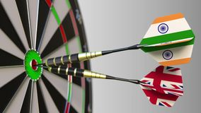 Flags of India and the United Kingdom on darts hitting bullseye of the target. International cooperation or competition. Animation stock footage