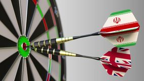 Flags of Iran and the United Kingdom on darts hitting bullseye of the target. International cooperation or competition. Animation stock video footage
