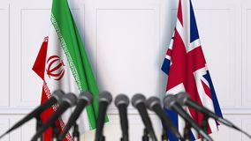 Flags of Iran and the United Kingdom at international meeting or negotiations press conference. 3D animation stock video footage