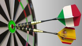 Flags of Italy and Spain on darts hitting bullseye of the target. International cooperation or competition conceptual 3D. Flags of Italy and Spain on darts Royalty Free Stock Images