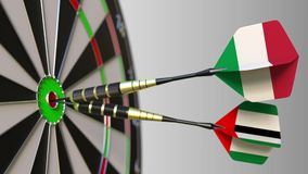 Flags of Italy and the UAE on darts hitting bullseye of the target. International cooperation or competition conceptual. Flags of Italy and the UAE on darts stock video footage