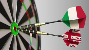 Flags of Italy and the United Kingdom on darts hitting bullseye of the target. International cooperation or competition. Animation stock footage