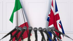 Flags of Italy and The United Kingdom at international meeting or negotiations press conference. 3D animation stock footage