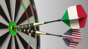 Flags of Italy and the USA on darts hitting bullseye of the target. International cooperation or competition conceptual Royalty Free Stock Images