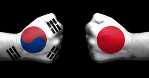 Flags of Japan and South Korea painted on two clenched fists facing each other on black background/.Japan–South Korea relations royalty free stock image