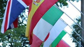 Flags from Japan, Spain, Italy, Brazil and England hanging in street stock video footage