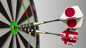Flags of Japan and the United Kingdom on darts hitting bullseye of the target. International cooperation or competition. Animation stock footage