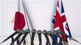 Flags of Japan and The United Kingdom at international meeting or negotiations press conference. 3D animation stock video