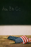 Flags laying on top of old school desk Stock Photos