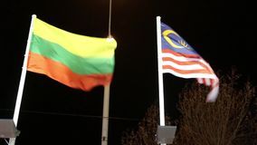 Flags of Lithuania and Malaysia with illumination on wind at night. Flags of Lithuania and Malaysia with illumination on wind at dark night stock video