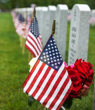 Flags at a National Cemetery. American flag and Red Roses at a veterans tombstone at an American National Cemetery Royalty Free Stock Photos
