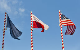 Flags of Nato, Poland and USA outdoor against clear blue sky. royalty free stock image