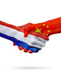 Flags Netherlands, China countries, partnership friendship handshake concept. royalty free stock photo