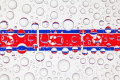 Water drops on glass and flags of North Korea royalty free stock photos