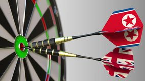 Flags of North Korea and the United Kingdom on darts hitting bullseye of the target. International cooperation or. Competition Royalty Free Stock Photos