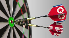Flags of North Korea and the United Kingdom on darts hitting bullseye of the target. International cooperation or. Competition animation stock video