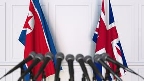 Flags of North Korea and The United Kingdom at international meeting or negotiations press conference. 3D animation stock video