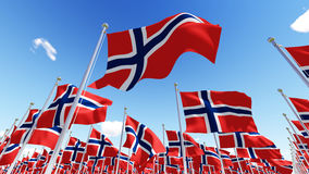 Flags of Norway waving in the wind against blue sky. Stock Image