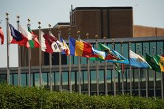 Flags outside united nations building in new york. Flags waving outside united nations building in manhattan new york stock image