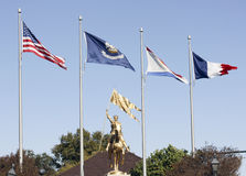 Flags Over Joan Of Arc Statue. Landscape of Joan of Arc statue under flags on Decatur Street in New Orleans, Louisiana Royalty Free Stock Image