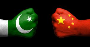 Flags of Pakistan and China painted on two clenched fists facing. Each other on black background/Pakistan - China relations concept stock photo