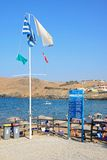 Flags on Panormos Beach, Crete. Greek flag and information board on the edge of the beach with views towards the rocky coastline, Panormos, Crete, Greece Royalty Free Stock Photography