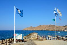 Flags on Panormos Beach, Crete. Flags and information boards on the edge of the beach with views towards the rocky coastline, Panormos, Crete, Greece, Europe Stock Images