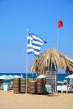 Flags and parasols on Potamos beach, Malia. Royalty Free Stock Photo