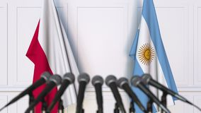 Flags of Poland and Argentina at international meeting or negotiations press conference. 3D animation stock footage