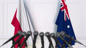 Flags of Poland and Australia at international meeting or negotiations press conference. 3D animation stock video