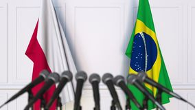 Flags of Poland and Brazil at international meeting or negotiations press conference. 3D animation stock footage