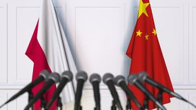 Flags of Poland and China at international meeting or negotiations press conference. 3D animation stock footage