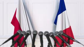 Flags of Poland and France at international meeting or negotiations press conference. 3D animation stock footage