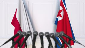 Flags of Poland and North Korea at international meeting or negotiations press conference. 3D animation stock footage
