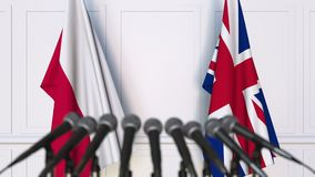 Flags of Poland and The United Kingdom at international meeting or negotiations press conference. 3D animation stock footage