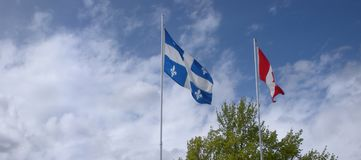 Flags of Quebec and Canada. Two North American flags on tall flagpoles flapping in the wind in the province of Quebec, Canada royalty free stock image